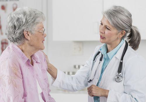 An elderly patient talks with her doctor.