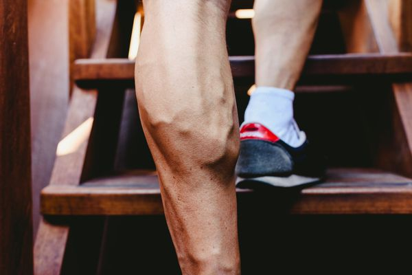 Large visible veins of calf muscles in a man's leg. - stock photo
