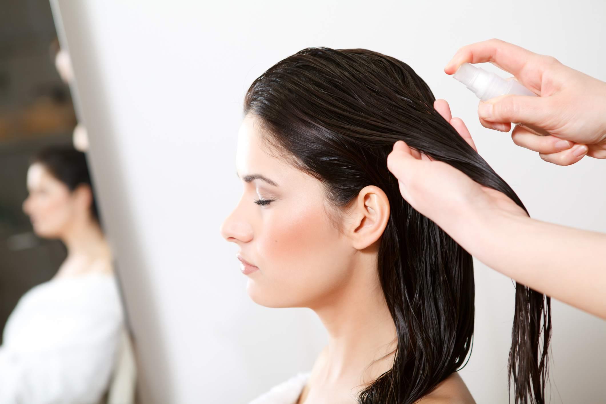 woman getting hair oil sprayed in her hair