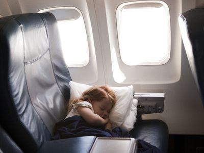 girl (2-3) sleeping in airplane seat