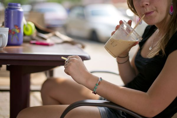 Teenage Girl Drinking Iced Coffee Drink Through Straw
