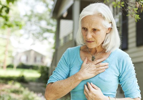 A woman uncomfortably holding her chest