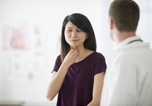A woman talking to her doctor about her throat pain