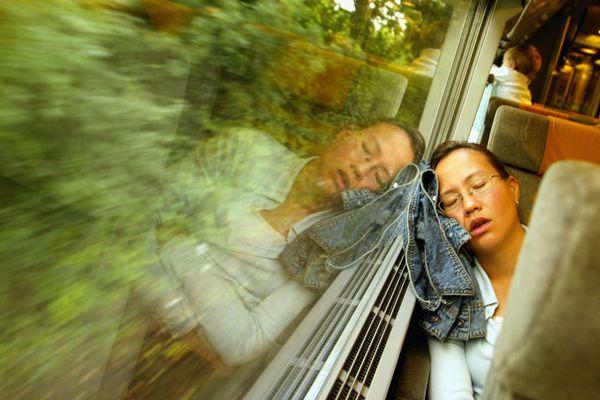 A woman sleeps against a train window