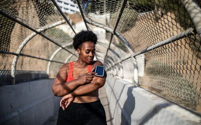 Healthy woman touching phone screen on armband before exercising outdoors