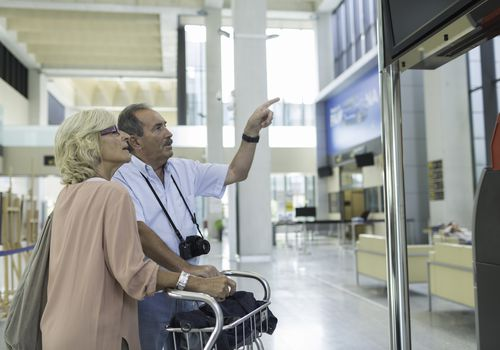 An older couple checking the screen at an airport