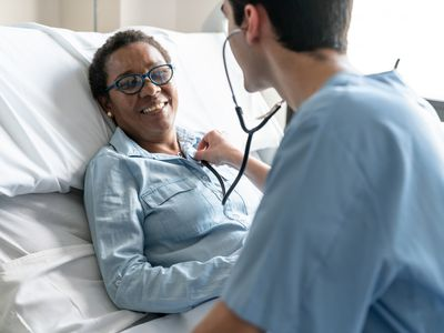 doctor checking woman with stethoscope