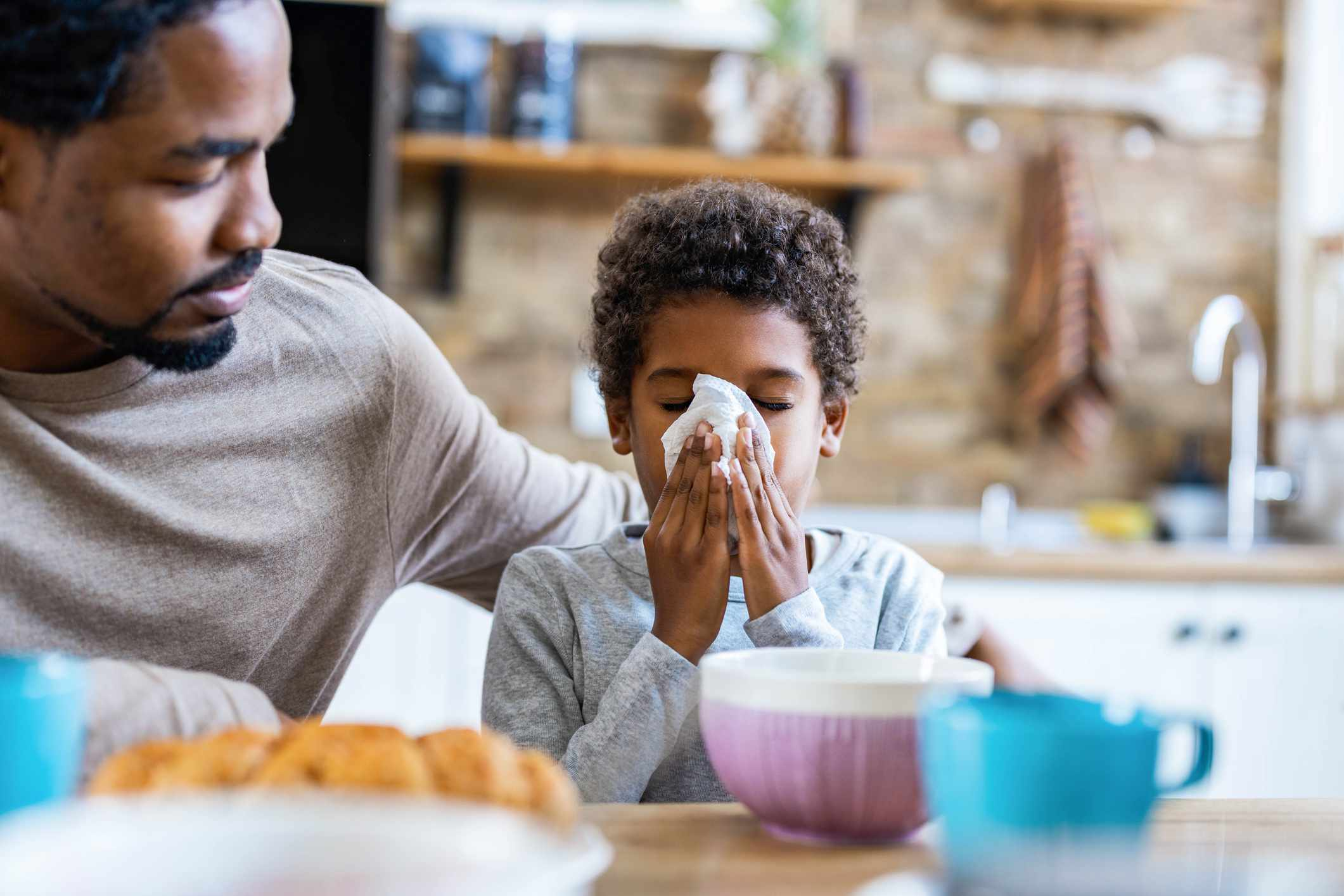 father and son with son holding tissue