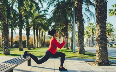 Woman doing lunges on park bench