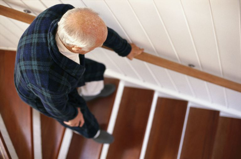 elderly man carefully descending stairs