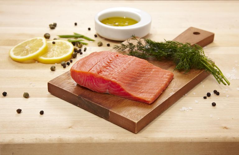 Salmon on acutting board with dill, lemon slices, and capers