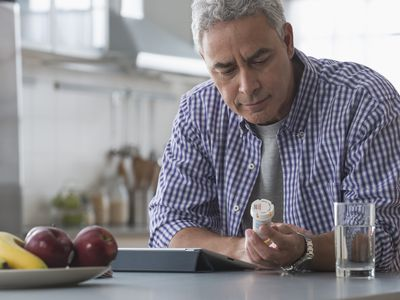 Hispanic man examining prescription bottle in kitchen