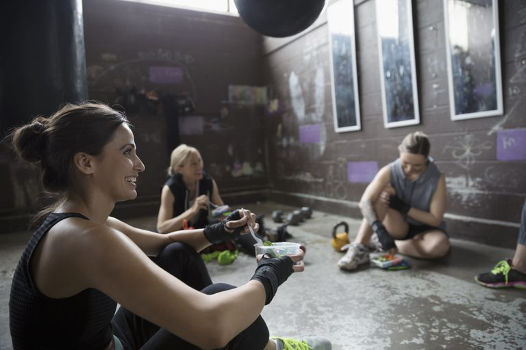 Female boxers resting, eating snack post workout at gritty gym with punching bags