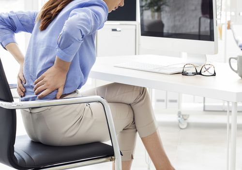 A white woman at an office leaning over at her chair due to back pain