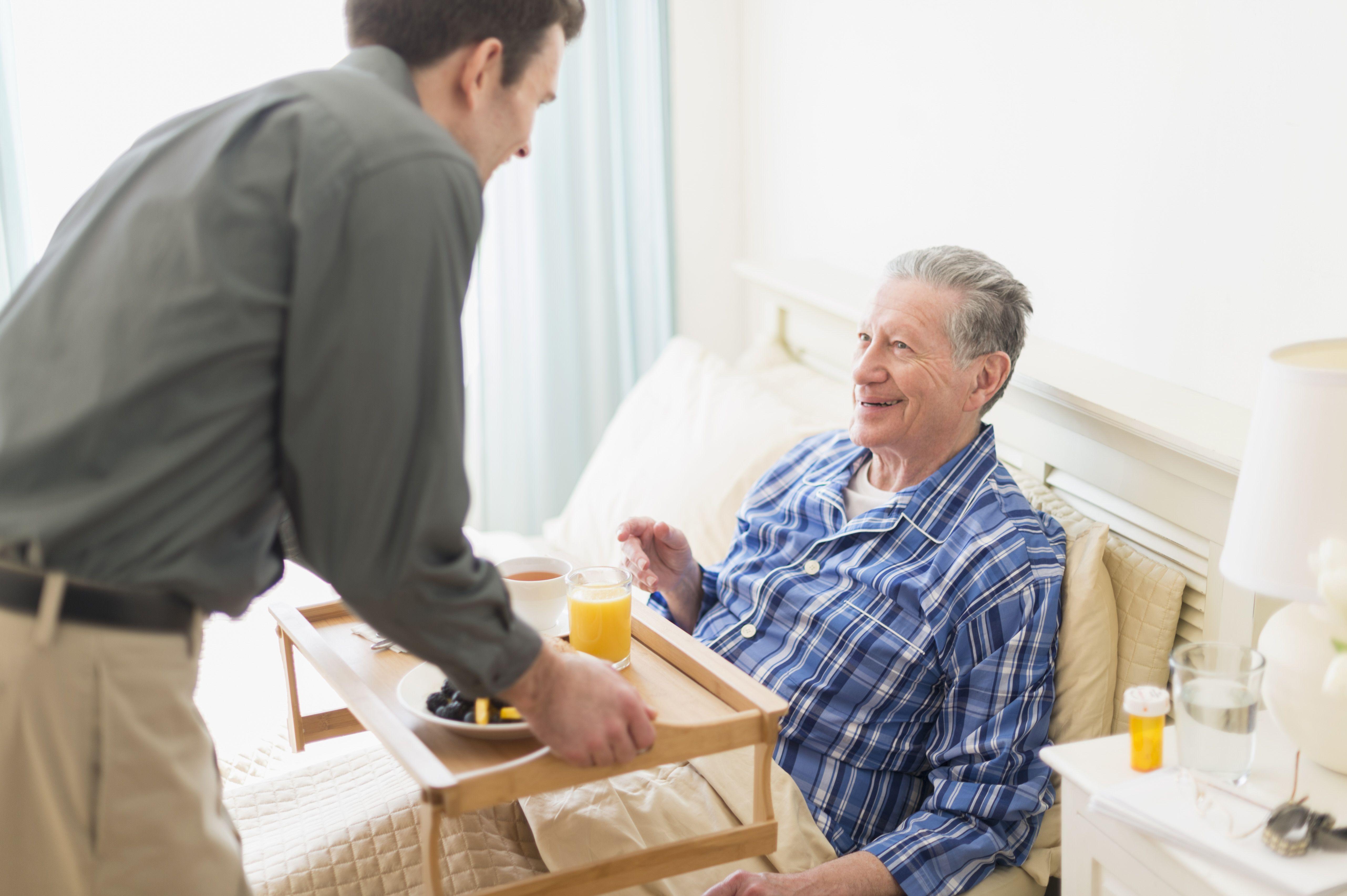 Senior Caucasian man having breakfast in bed