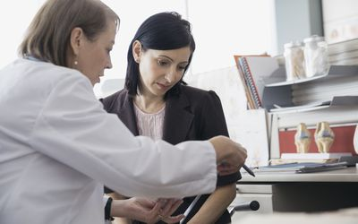 Concerned patient reviewing a tablet with doctor