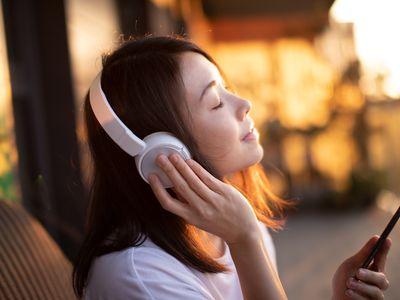 Young Woman Enjoying Music Over Headphones And Using Smart Phone