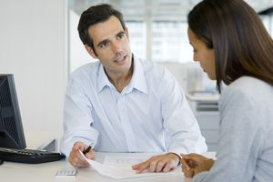 Man explaining something to a woman while pointing at a piece of paper.