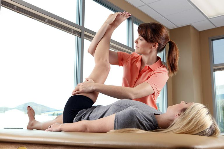 A physical therapist working a a young woman's hip or leg.