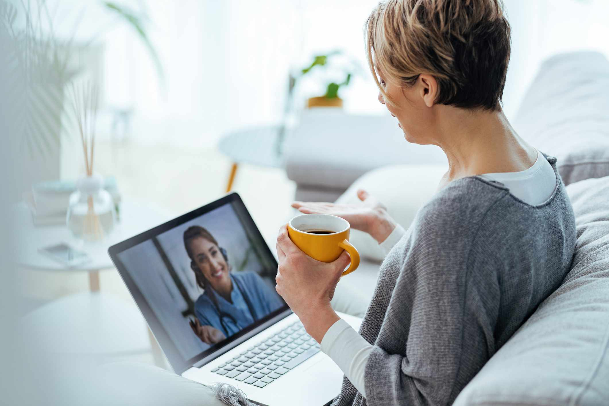 Woman sitting on the sofa while making video call over laptop with her doctor