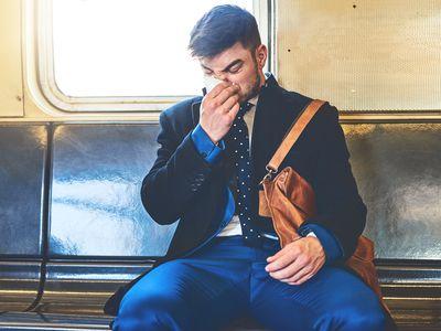 man sneezing on the train