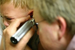 doctor examining toddler's ear for mastoiditis