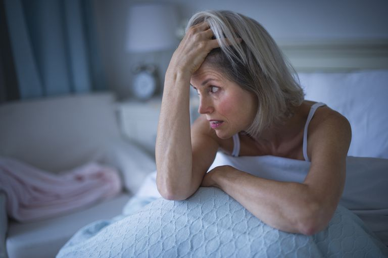 Older woman looking anxious in bed