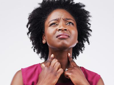 Studio shot of a young woman suffering with a sore throat against a grey background