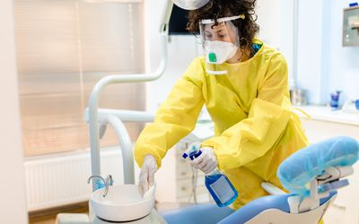 A dentist cleaning down the space during COVID-19 pandemic.