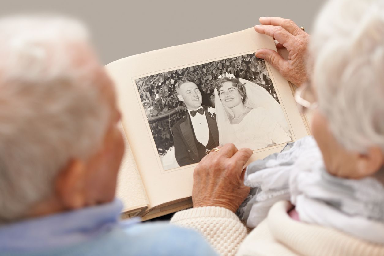 An older couple looking at their wedding photos