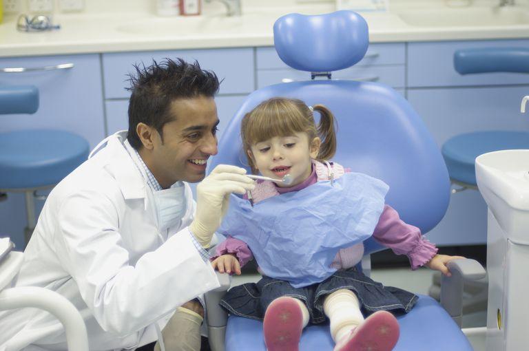 Preschool aged girl having her teeth examined by a dentist