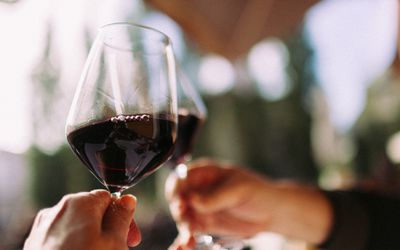 Red wine in two glasses being clinked together