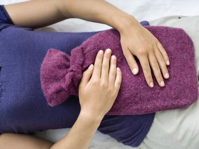 Young woman holding a hot water bottle on her stomach