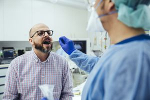 doctor taking swab of patient's mouth