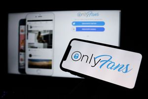 a phone screen showing the onlyfans logo in front of a computer screen open to the onlyfans log in page