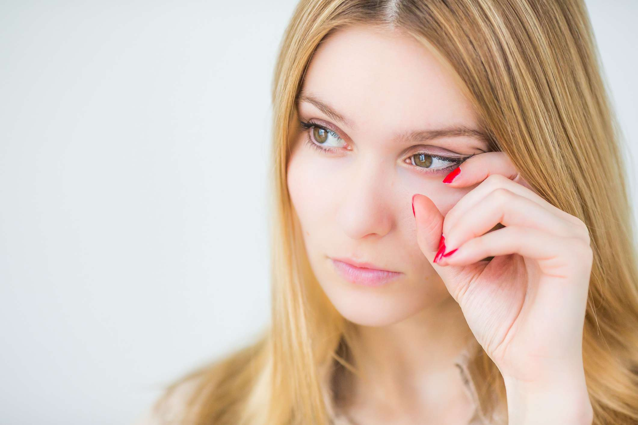 Woman on a white background scratching the corner of her eye