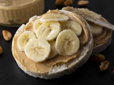 Peanut butter and banana on rice cakes, healthy, dietary food. Black background.