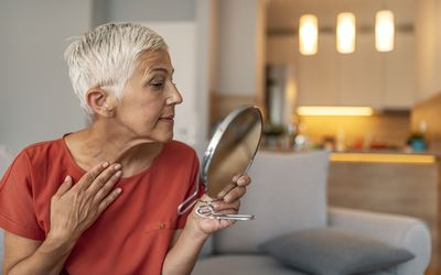 Mature woman with make-up mirror massaging her face and neck - stock photo