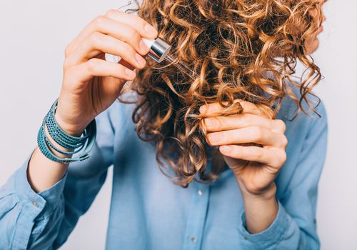 Young woman holding pipette with oil applying on her curly hair