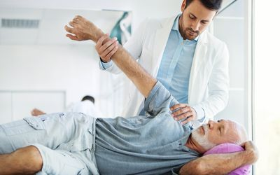 A doctor is examining a patient's shoulder while he lies on a table