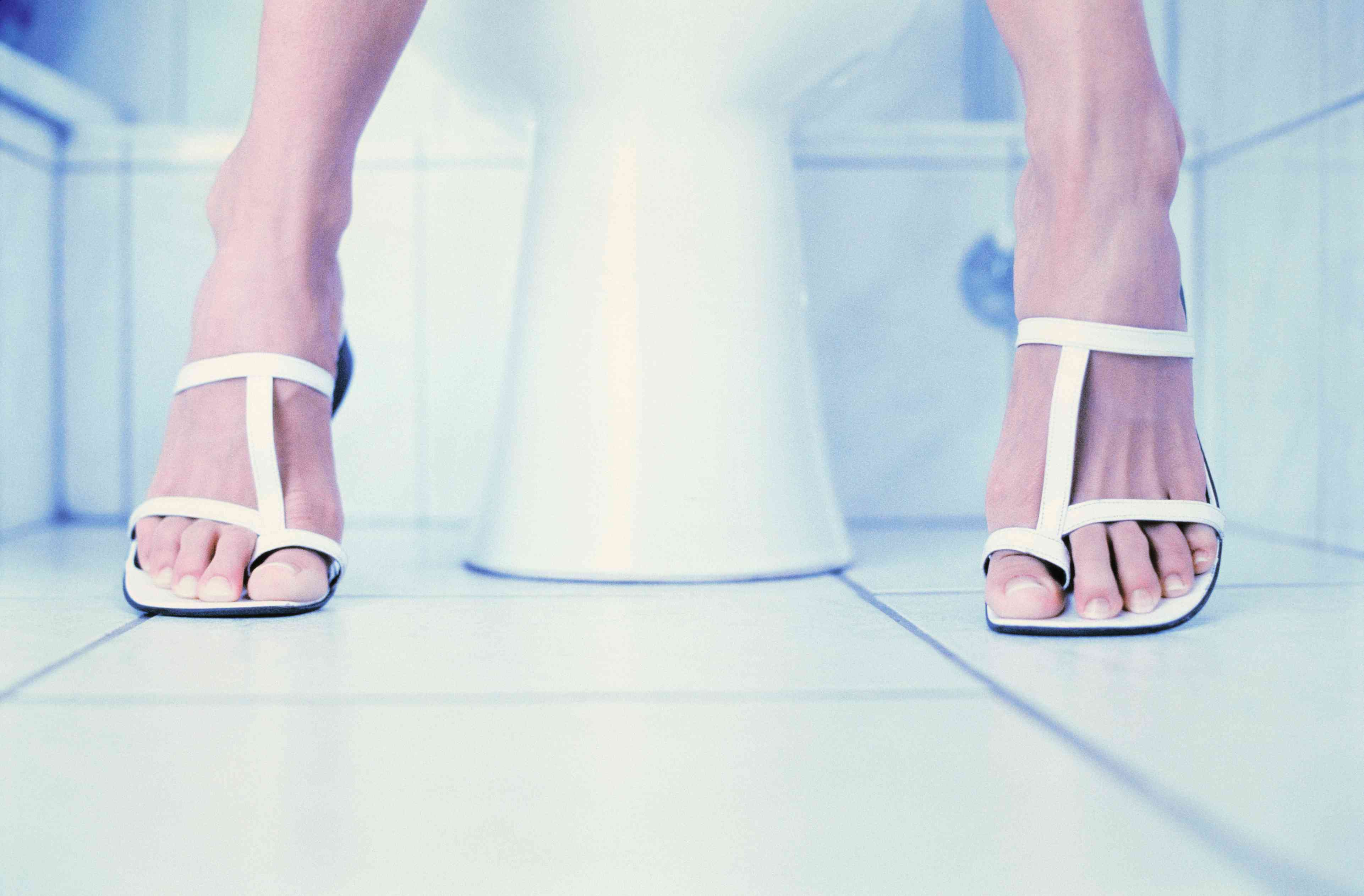 Woman's feet next to toilet in bathroom