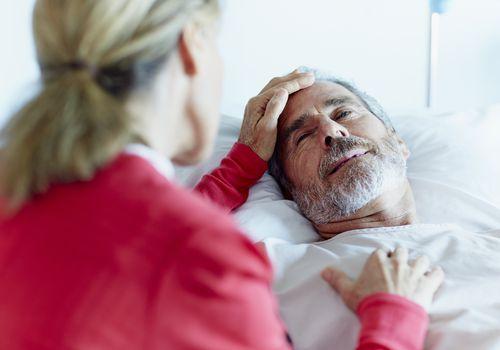 Woman caressing ill man in hospital ward