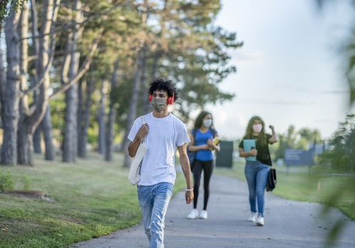 Students walking on campus wearing face masks.
