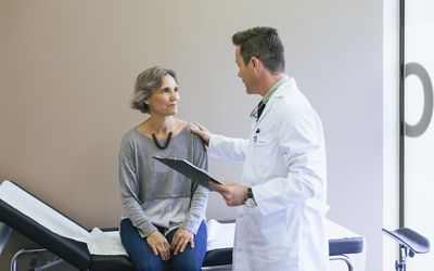 Smiling patient talking with doctor while sitting on bed at hospital