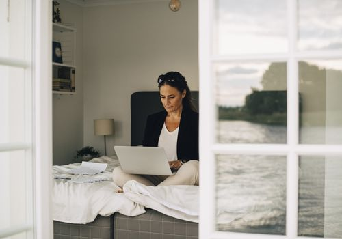 Woman in bed on the computer