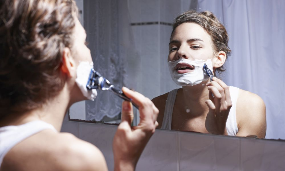 woman shaving face in mirror