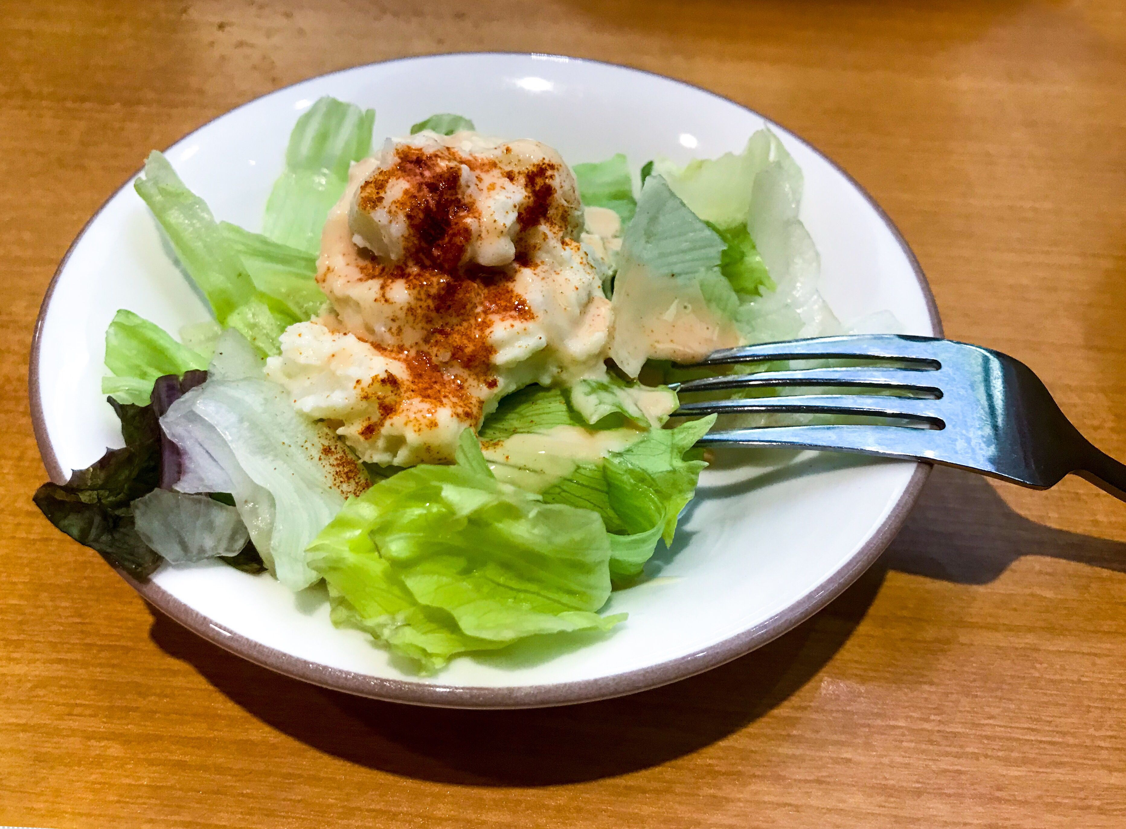 Small salad with fork on table