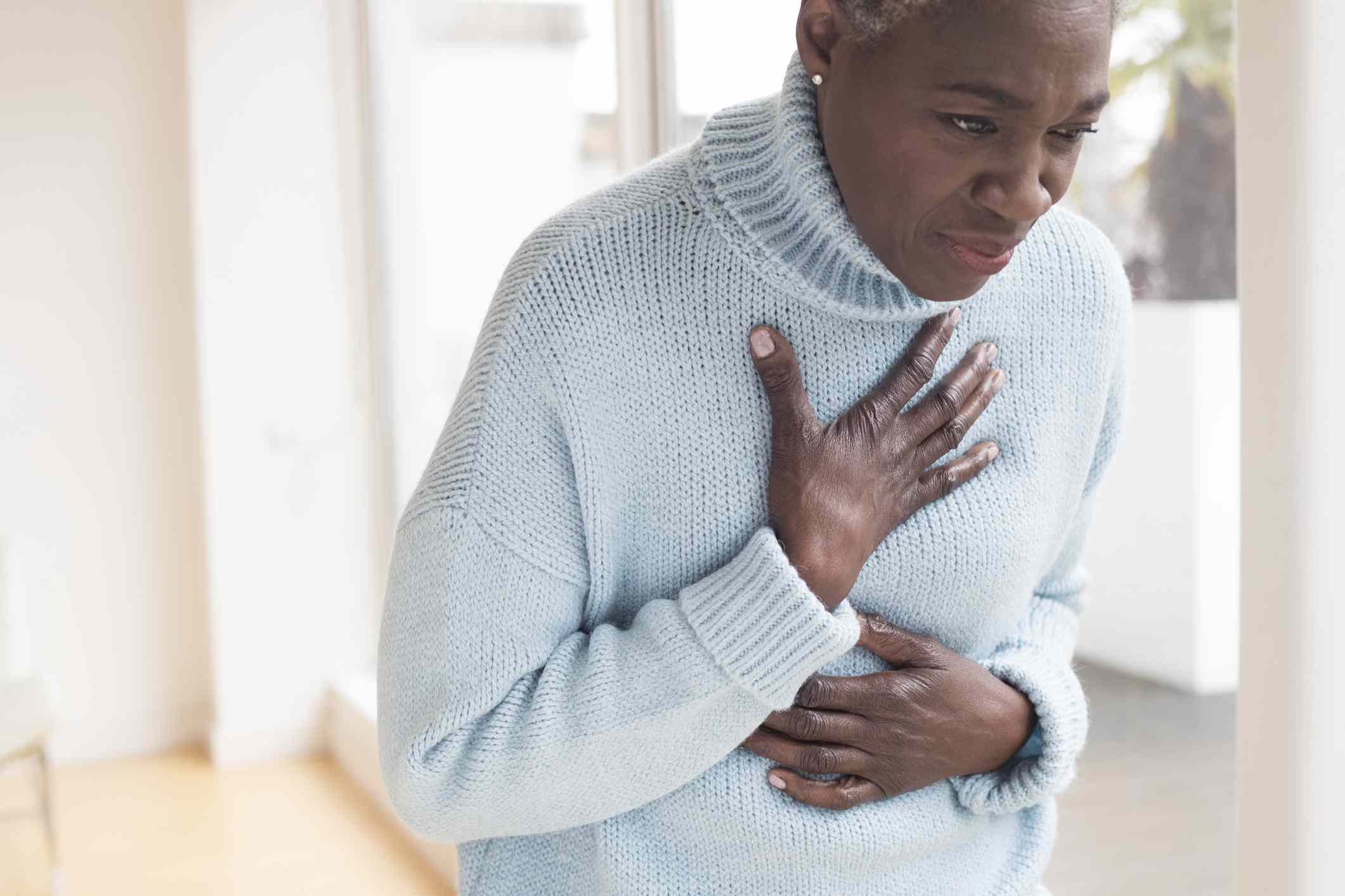 Woman touching chest in pain
