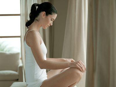 Woman sitting cross-legged on chair
