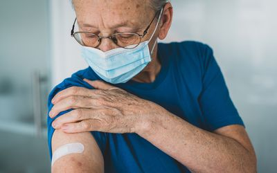 Older man looking at his arm where he was vaccinated.